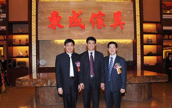 中国家具协会理事长朱长岭(中)、大涌党员委员谢巧明(左)莅临东成展厅参观指导,并与总经理张锡复(右)合影留念